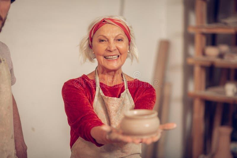 显示您泥罐的愉快的年迈的妇女 免版税图库摄影