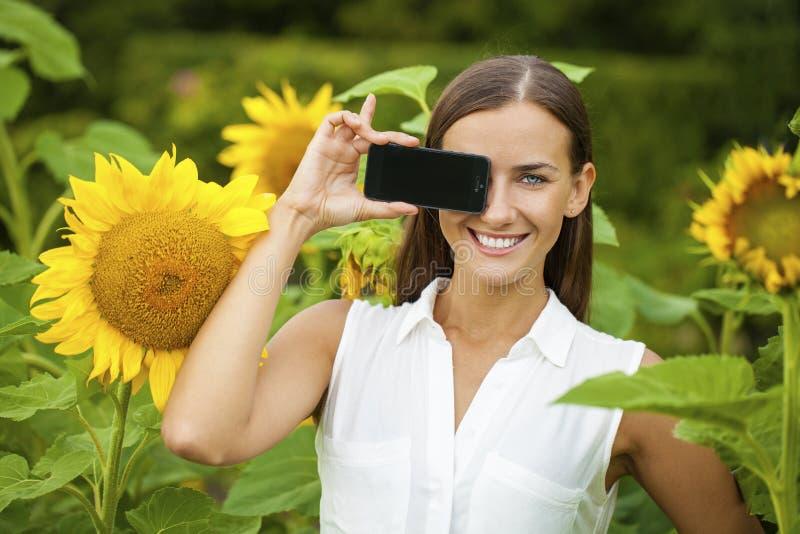 显示您的智能手机屏幕的年轻美丽的女孩 免版税库存照片
