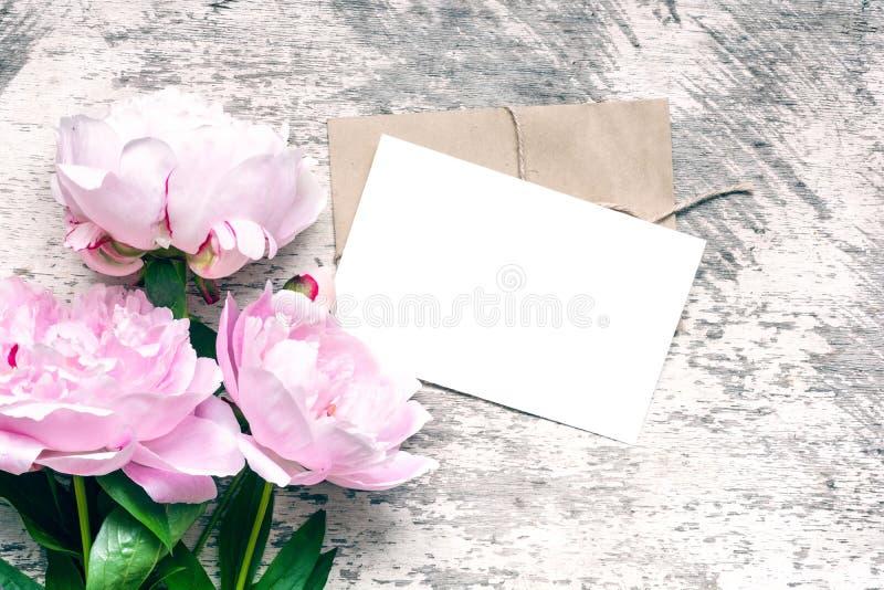 显示您的艺术品的时髦的烙记的大模型 空白的贺卡或婚礼邀请与桃红色牡丹开花 库存照片