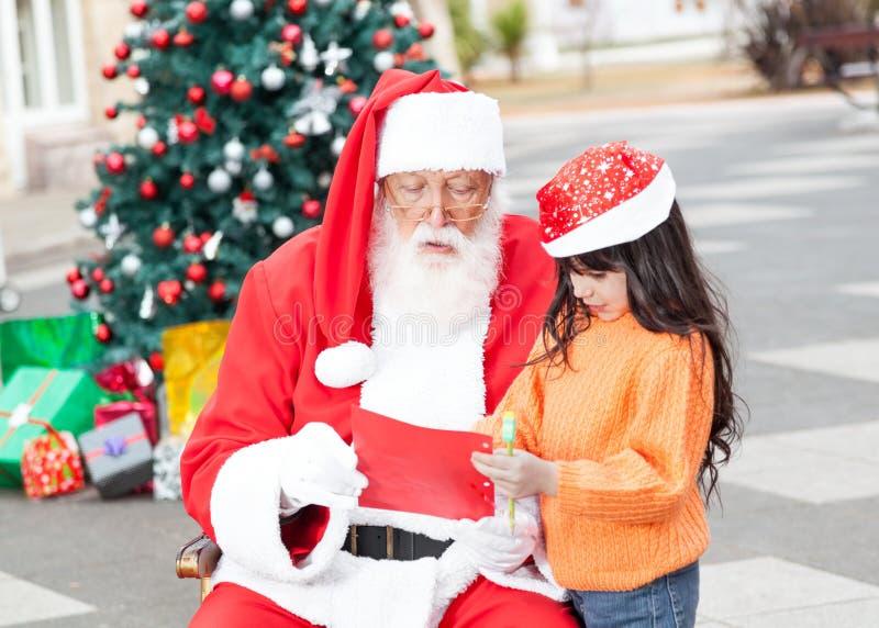 显示愿望的女孩对圣诞老人 免版税库存照片