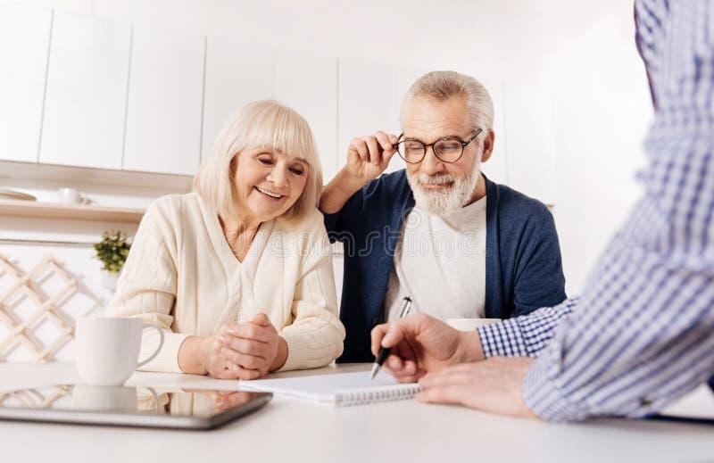显示房子布局的创造性的代理对客户年迈的夫妇  免版税库存图片