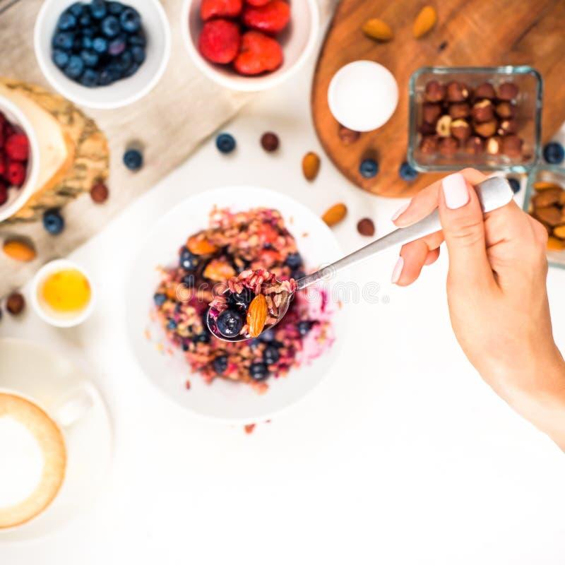 显示手的顶视图吃与蜂蜜坚果,在白色木桌选择聚焦的蓝莓的粥,被弄脏 库存图片