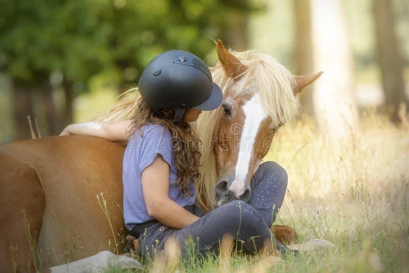 显示把戏的女孩和她美丽的栗色小马学会与自然驯马 免版税库存图片