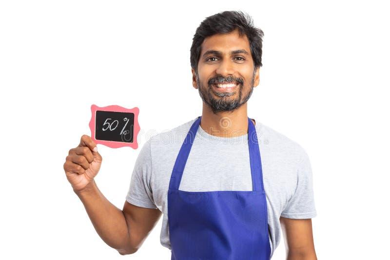 显示折扣标志的超级市场雇员 免版税库存照片