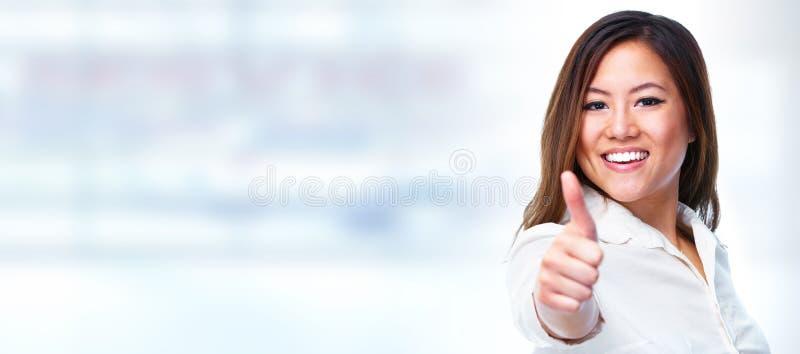 显示拇指的亚裔女商人 免版税库存图片