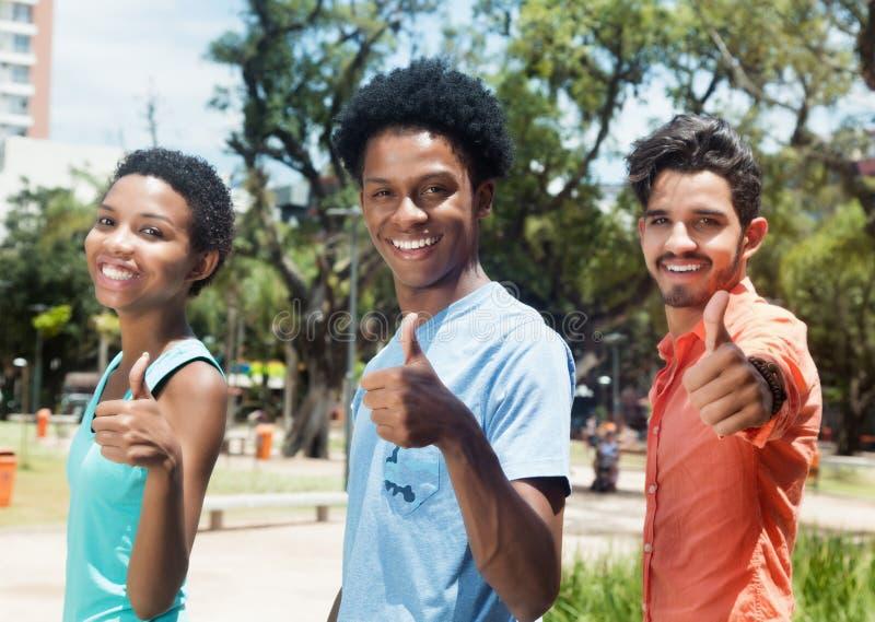 显示拇指的小组三个拉丁美洲的年轻成人在城市 免版税库存图片