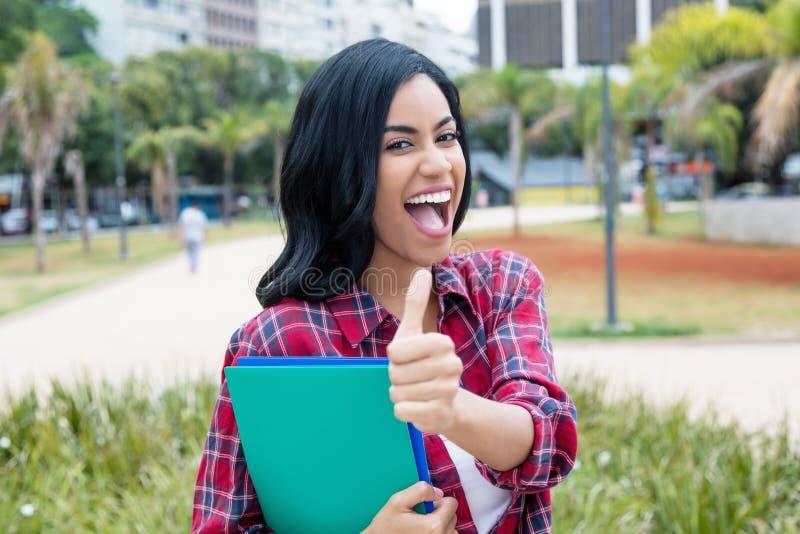 显示拇指的成功的当地拉丁美洲的女学生 免版税库存图片