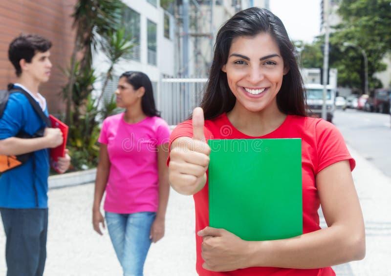显示拇指的红色衬衣的愉快的拉丁女学生 库存照片