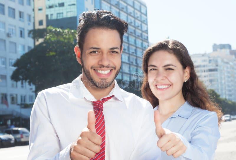 显示拇指的聪明的年轻企业队在城市 免版税库存照片