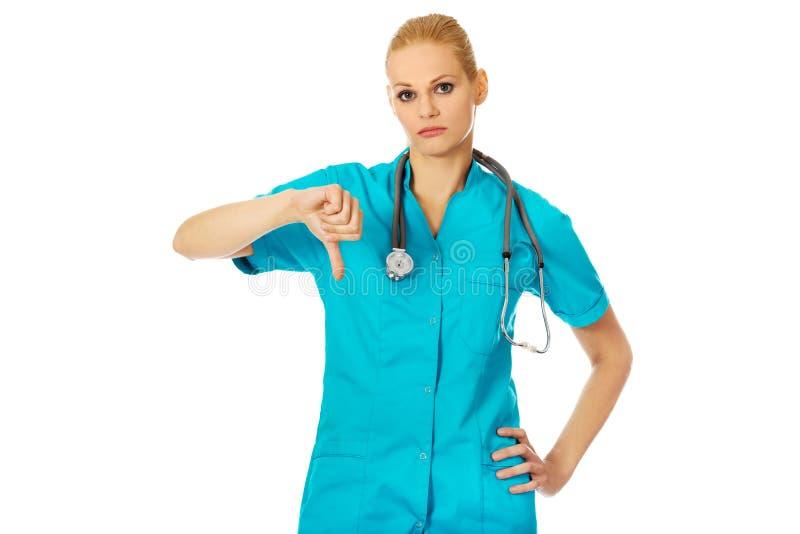 显示拇指的年轻不快乐的女性医生或护士下来 免版税库存照片