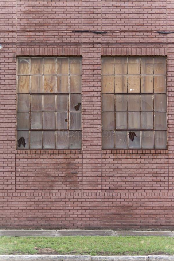 显示放弃的迹象与两的老红砖大厦猛击了窗口 图库摄影