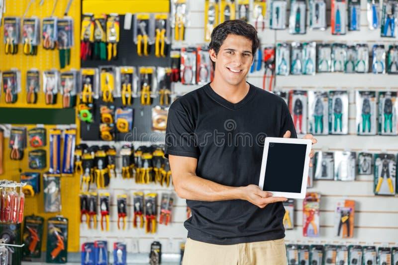 显示数字式片剂的人在五金店 库存照片