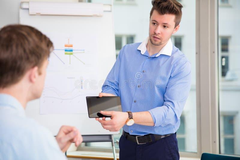 显示数字式片剂的商人对男性同事 库存图片