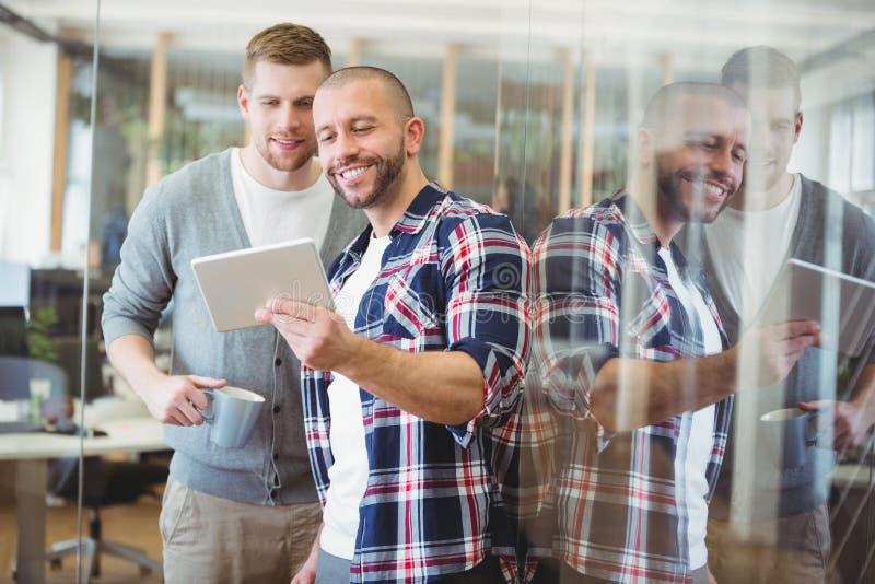 显示数字式片剂的商人正面图对同事 免版税库存图片
