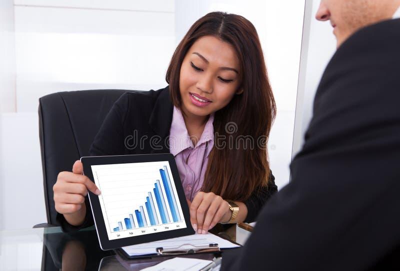显示数字式片剂的女实业家对同事 库存图片