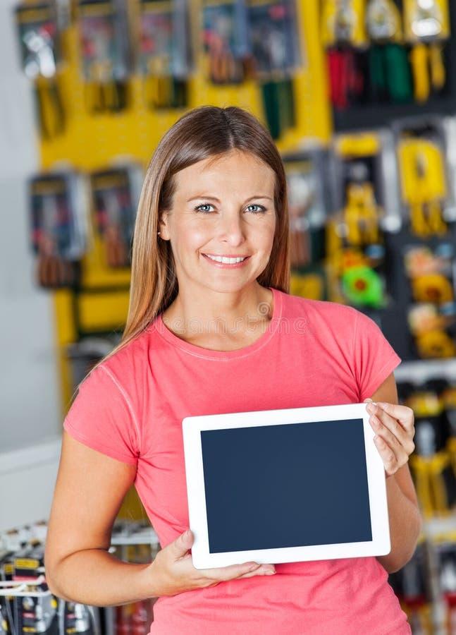 显示数字式片剂的妇女在五金店 免版税库存图片