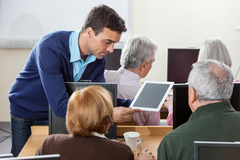 显示数字式片剂的老师对资深学生在计算机分类 免版税图库摄影