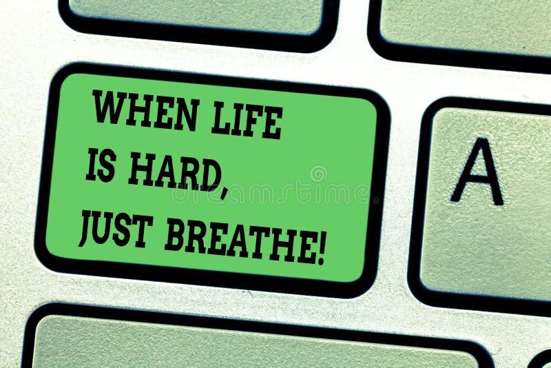 显示文本的标志,当生活艰苦是呼吸 概念性照片休假克服困难键盘键 免版税库存照片