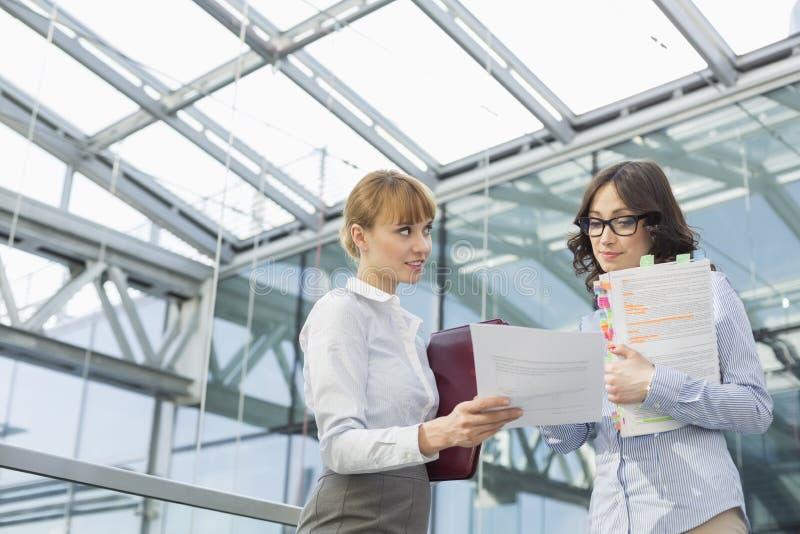 显示文件的中间成人女实业家对女性同事在办公室 免版税库存图片