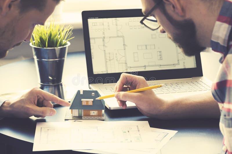 显示新房模型的建筑师对顾客在办公室 免版税库存图片