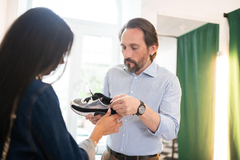 显示新的运动鞋的英俊的深色头发的人对妻子 免版税图库摄影