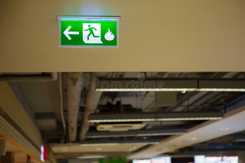 显示方式的绿色紧急出口标志逃脱 在大厦的太平门 库存图片