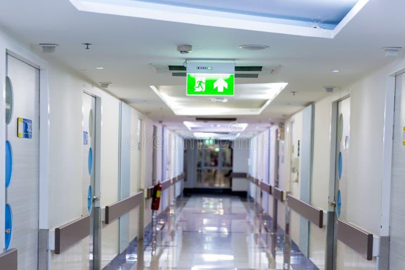 显示方式的绿色紧急出口标志逃脱 在大厦的太平门 免版税库存照片