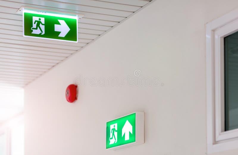 显示方式的绿色紧急出口标志逃脱 在大厦的太平门 库存照片