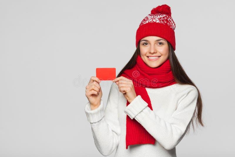 显示无具体金额的信用证卡片,冬天概念的微笑的妇女 红色拿着卡片的帽子和围巾的愉快的女孩,被隔绝在灰色backgrou 免版税库存照片