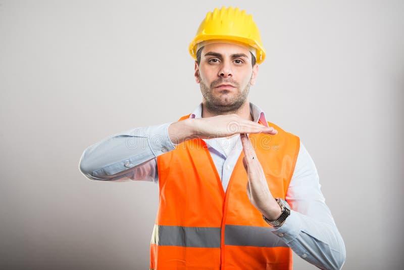 显示时间的年轻建筑师画象打手势 库存照片