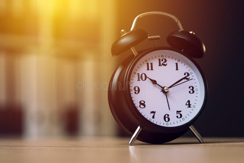 显示时间的经典闹钟在工作时间在办公室 免版税库存图片