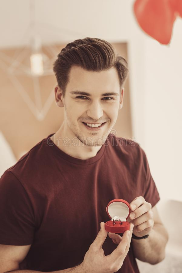 显示昂贵的定婚戒指的激动的微笑的人对他的最好的朋友 免版税图库摄影