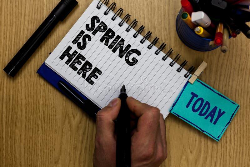 显示春天的文字笔记在这里 陈列在冬天季节以后的企业照片到达了享受自然花太阳人holdin 免版税库存图片