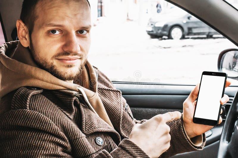 显示智能手机或手机的年轻英俊的微笑的人白色屏幕作为嘲笑为坐您的产品在汽车 免版税库存照片