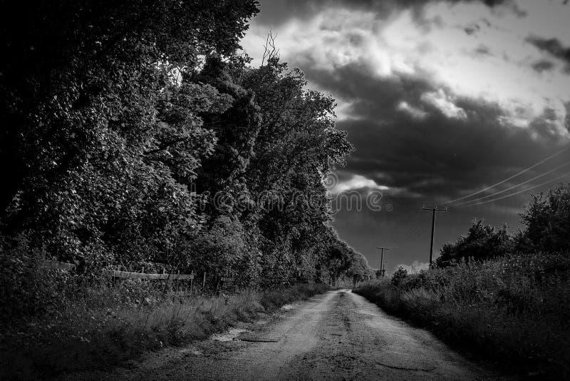显示暴风云会集的一条农村泥铺跑道车道的邪恶的看法 免版税库存图片