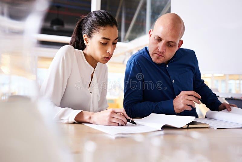 显示最新的进展的年轻聪明的女实业家对她的男性伙伴 免版税库存照片