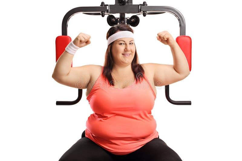 显示有一个行使的机器的肥头大耳的妇女肌肉 库存照片