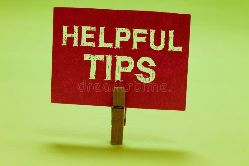 显示有用的技巧s的文本标志是 概念性照片要求专家的解答咨询警告晒衣夹的提示拿着红色纸 免版税库存图片