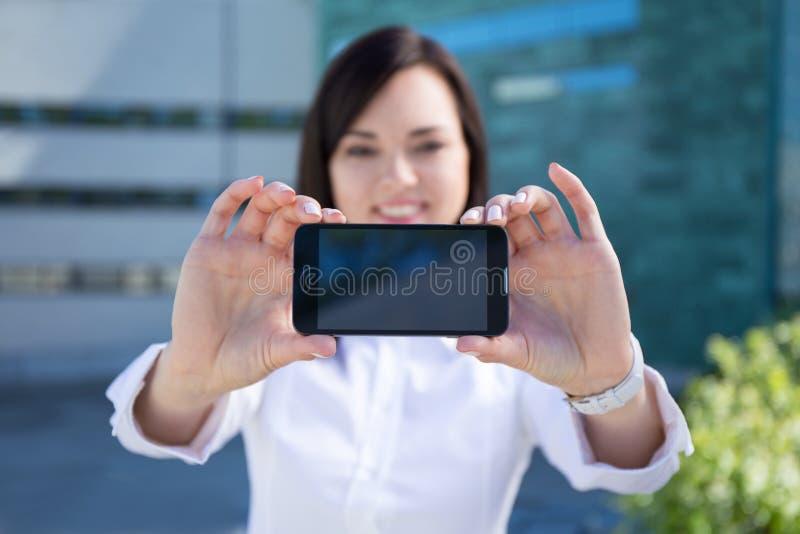 显示有空白的scr的年轻美丽的女商人智能手机 免版税库存照片
