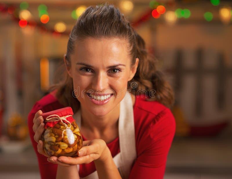 显示有蜂蜜坚果的愉快的年轻主妇画象瓶子 免版税图库摄影