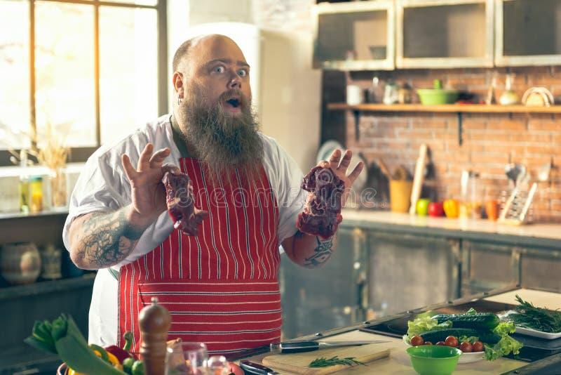 显示未加工的食物的激动的厚实的人在烹调前 免版税图库摄影