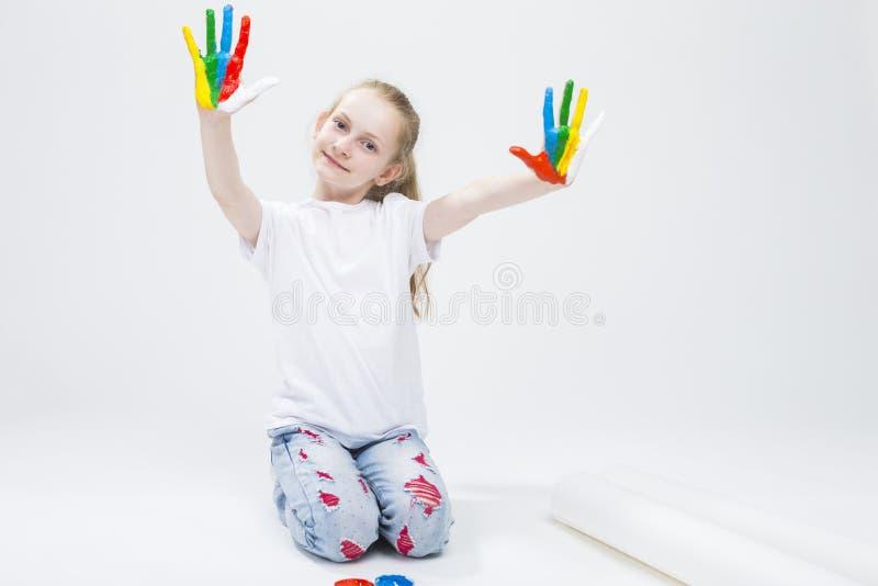 显示杂乱五颜六色的手的滑稽的女孩画象明亮地被绘在油漆工艺期间 图库摄影