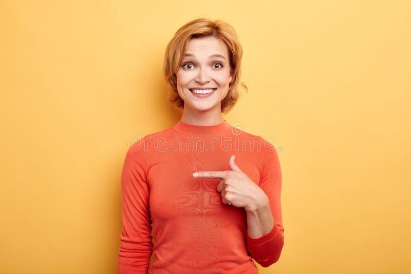 显示某事与食指的快乐的华美的金发女孩 免版税库存照片