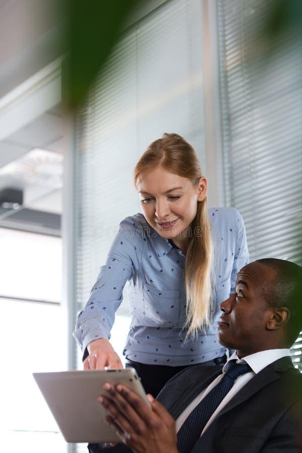 显示某事在数字式片剂的少妇对男性同事在办公室 图库摄影