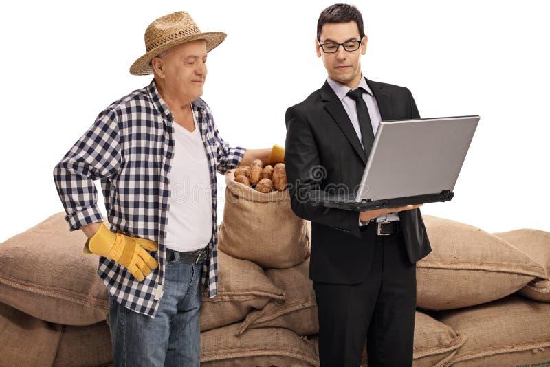 显示某事在膝上型计算机的年轻商人对农夫 免版税图库摄影