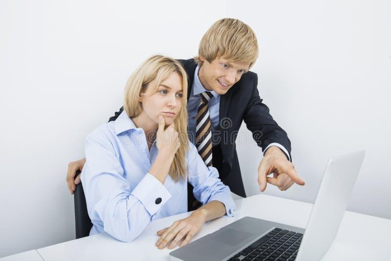 显示某事的商人对膝上型计算机的工友在办公室 库存照片
