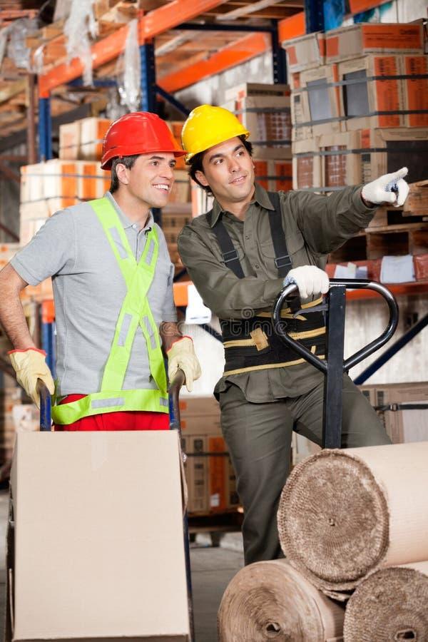 显示某事的工头对工友在仓库 免版税库存照片