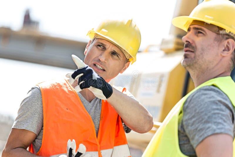 显示某事的监督员对同事在建造场所在晴天 免版税库存图片