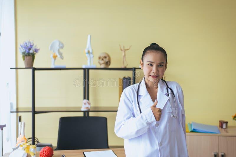 显示标志的微笑的美丽的亚裔妇女医生画象重击在医院,愉快和积极态度 库存图片