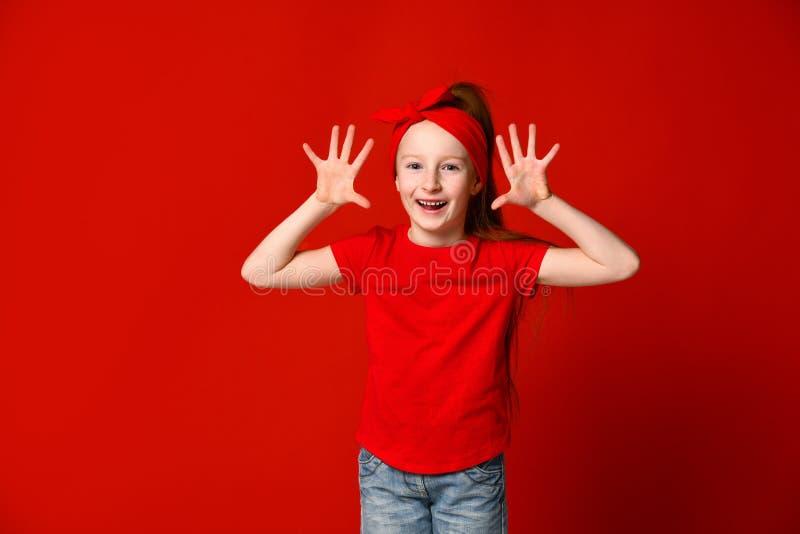 显示棕榈和滑稽的鬼脸的可爱的学龄前儿童女孩 获得逗人喜爱的快乐的孩子乐趣 : 乐趣概念 免版税库存图片
